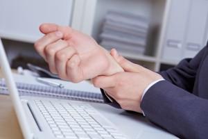 Hände mit Sehnenscheidenentzündung am Schreibtisch über Tastatur